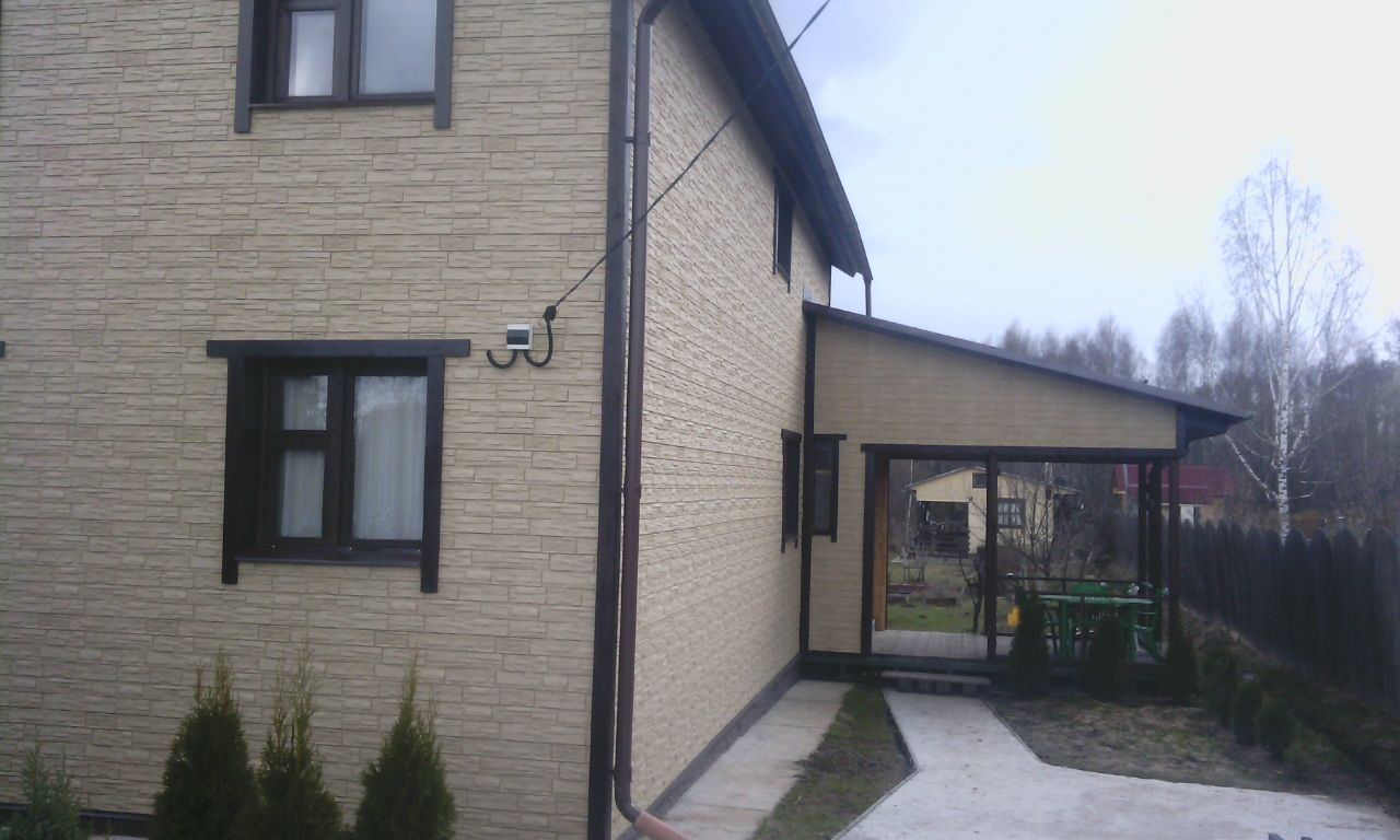 Обшивка дома фасадными панелями, монтаж водосточной системы